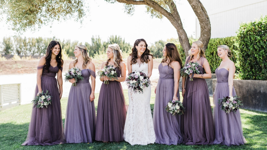 Brunette bride in lace wedding dress six bridesmaid in different purple hue tulle rosalie dresses revelry love wedding day