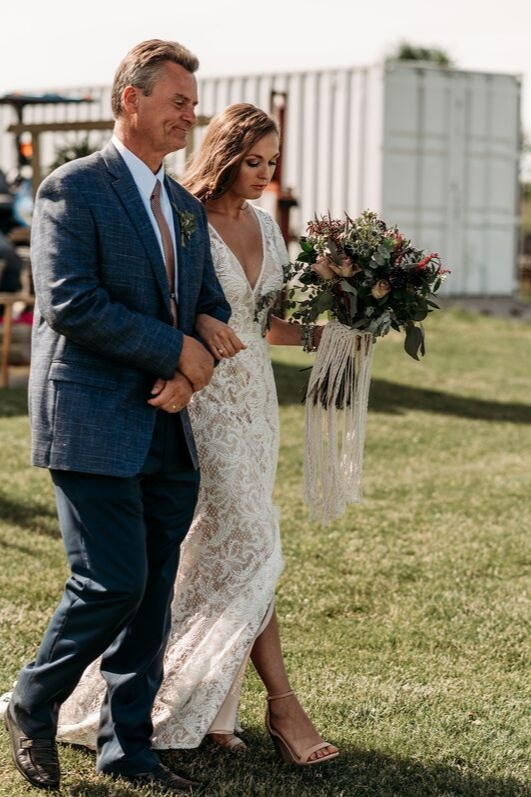 Brunette bride walking down aisle with father on wedding day in lace bridal gown holding flowers and boho bouquet side angle photo