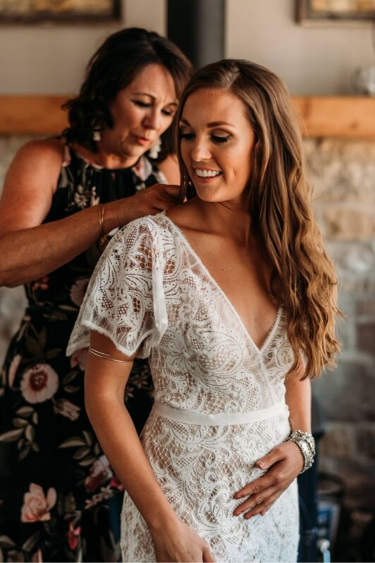 Brunette bride wearing lace wedding dress gets ready for wedding with mother zipping her up vintage gown