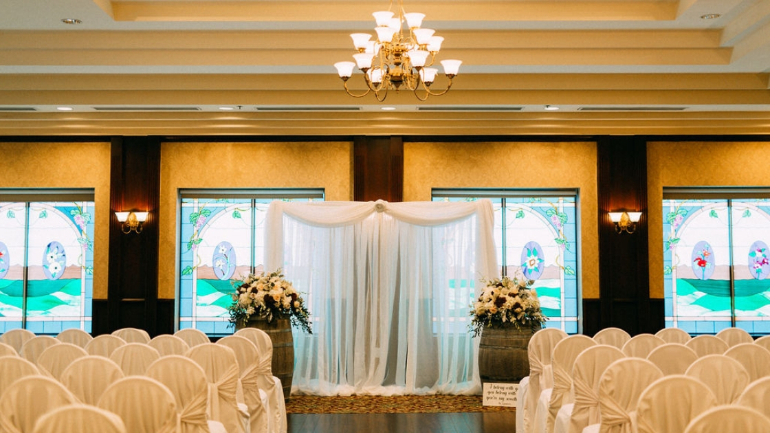 Ceremony space chandelier white chair covers hotel ballroom flowers empty space before ceremony wedding