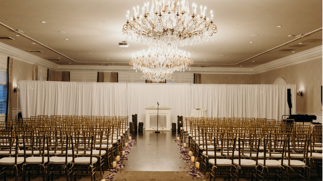 Ceremony space white background chandelier gold and white chairs aisle purple roses candles