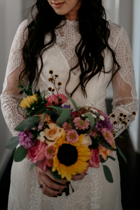 Close up bride bohemian in lace wedding gown bouquet sunflowers pinks purples greenery close up image
