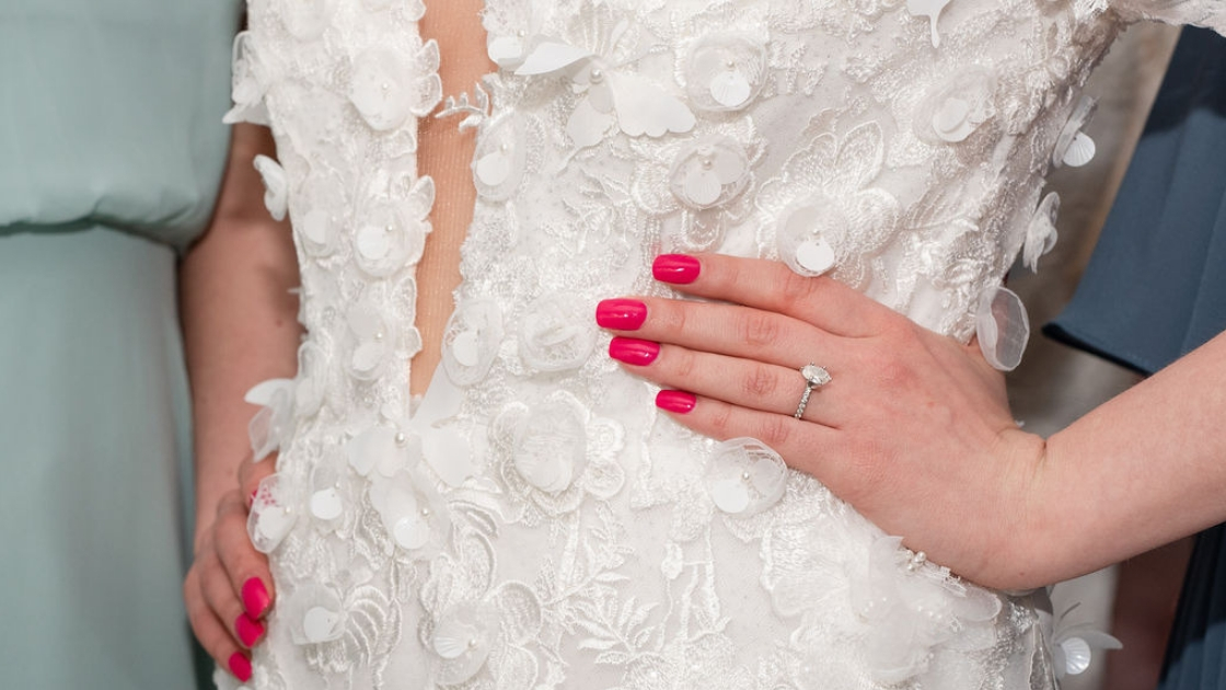 Closeup of aphrodite lace floral flower pearl bridal gown deep v lace pink nails with engagement ring