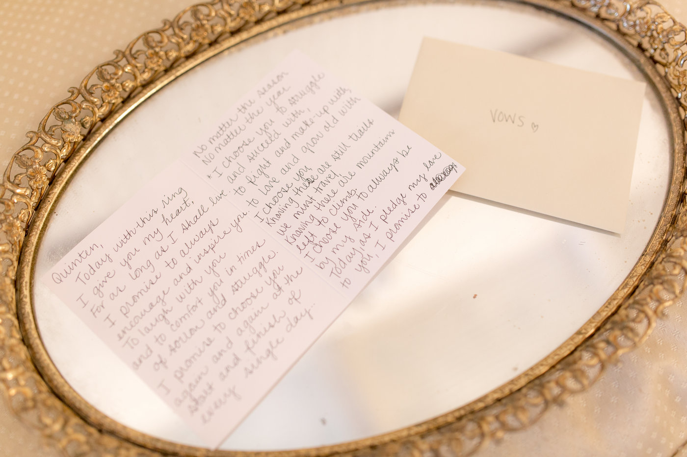 Vows and letters written to groom on gold mirror placed out on wedding day