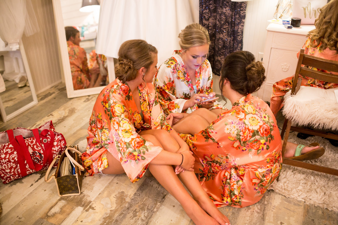 Bride and bridesmaids in robes get ready on wedding day