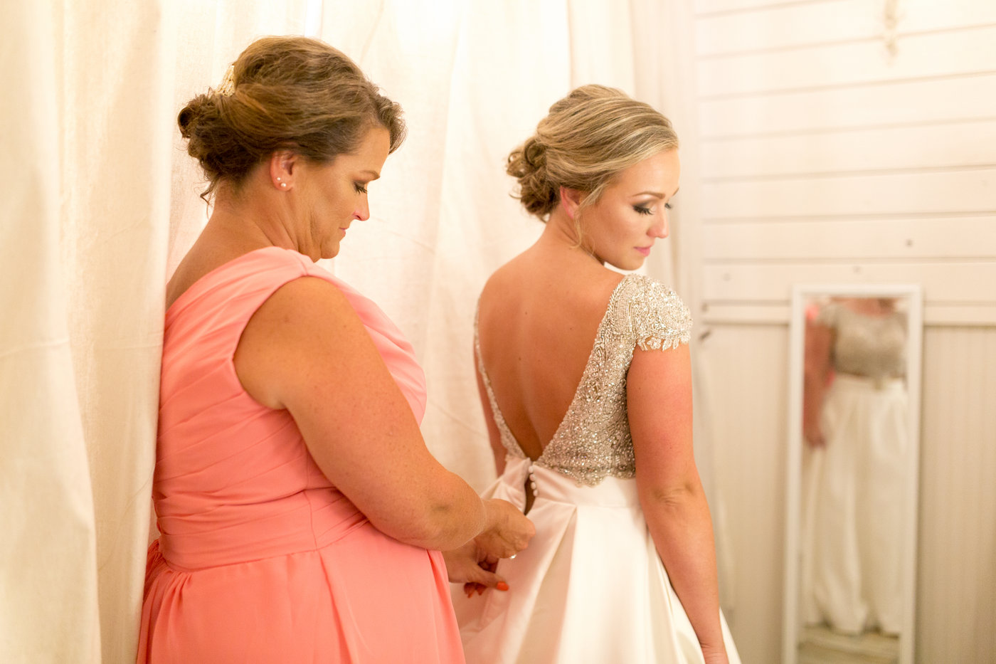 Bride's mom in pink zips up her daughters dress on her wedding day