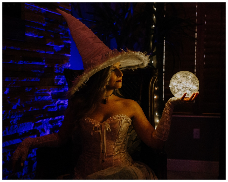 White witch with corset and gloves holds a crystal ball orb