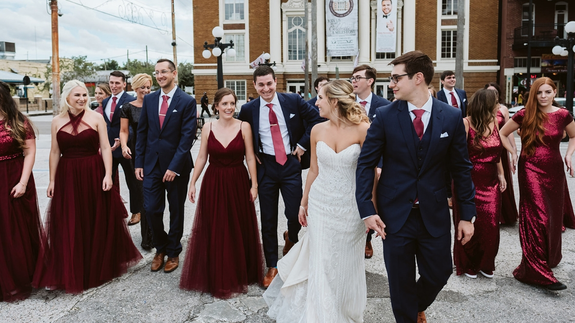 Curvy bride in white art deco wedding dress in groom and groomsmen in navy suists bridesmaids in burgundy revelry gowns