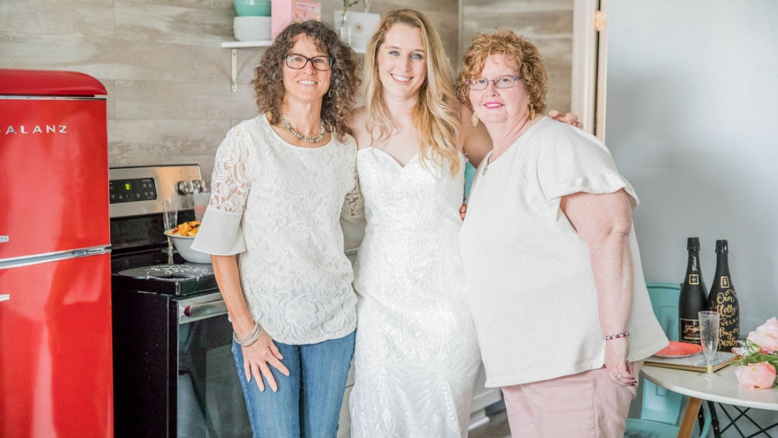 Dee blonde finally the bride decklyn bridal gown white wedding dress bridal gown pose with mother and mother in law at revelry try on party airbnb three people pose