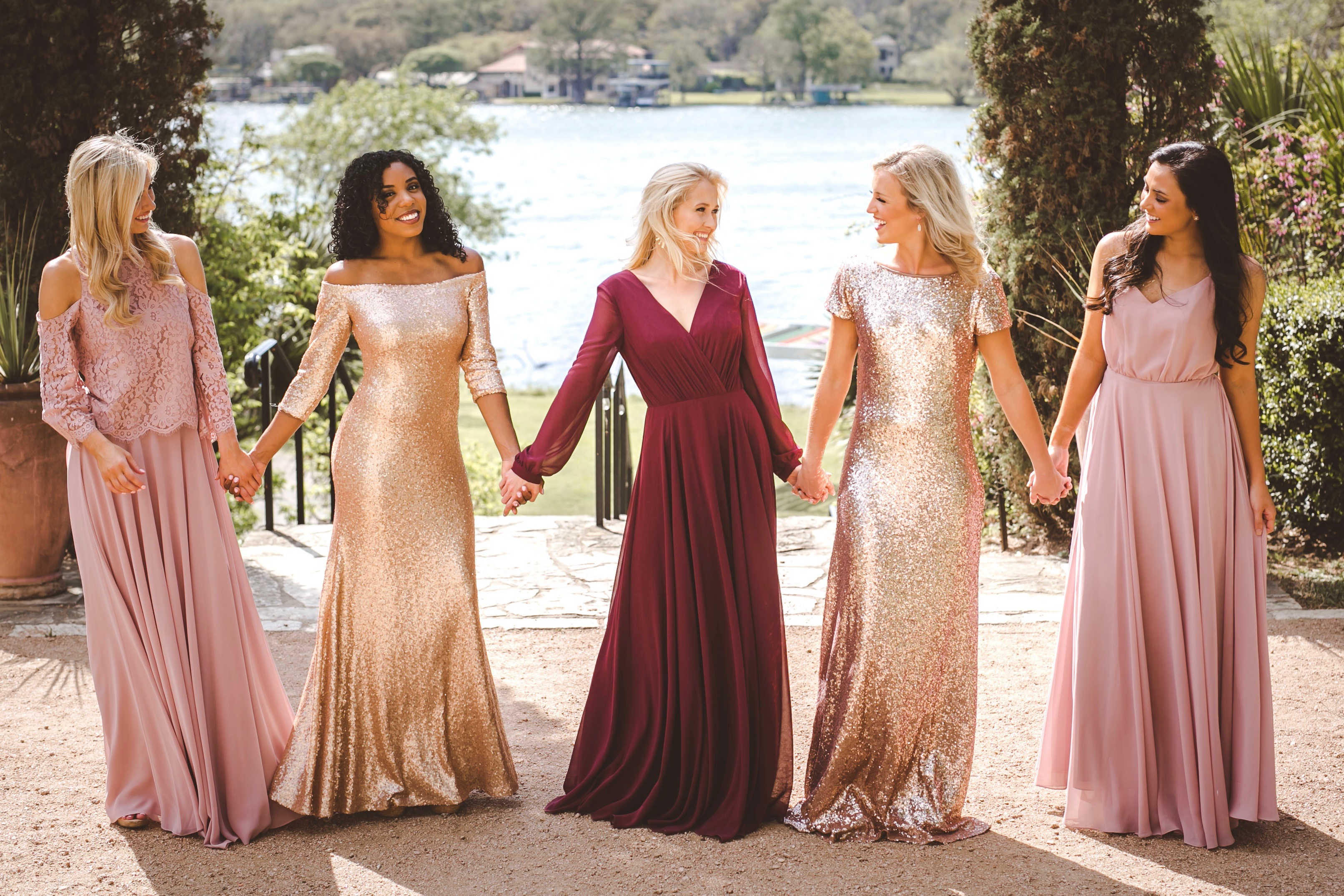 Bridesmaids in blush, gold, and burgundy dress styles in different Revelry fabrics come together for fall looks