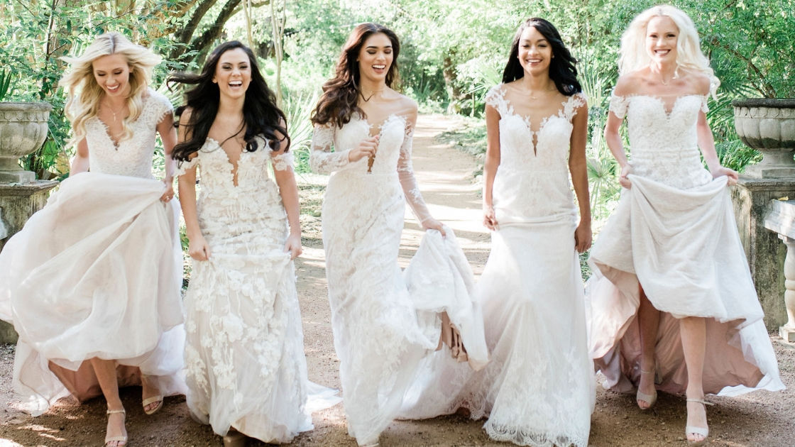 five beautiful brides in revelry wedding dresses running and laughing in white chiffon tulle dresses lace off the shoulder