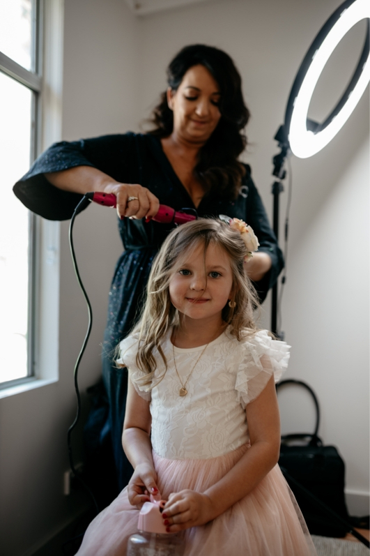 flower girl in pink tulle skirt getting hair curled with flowers in her hair