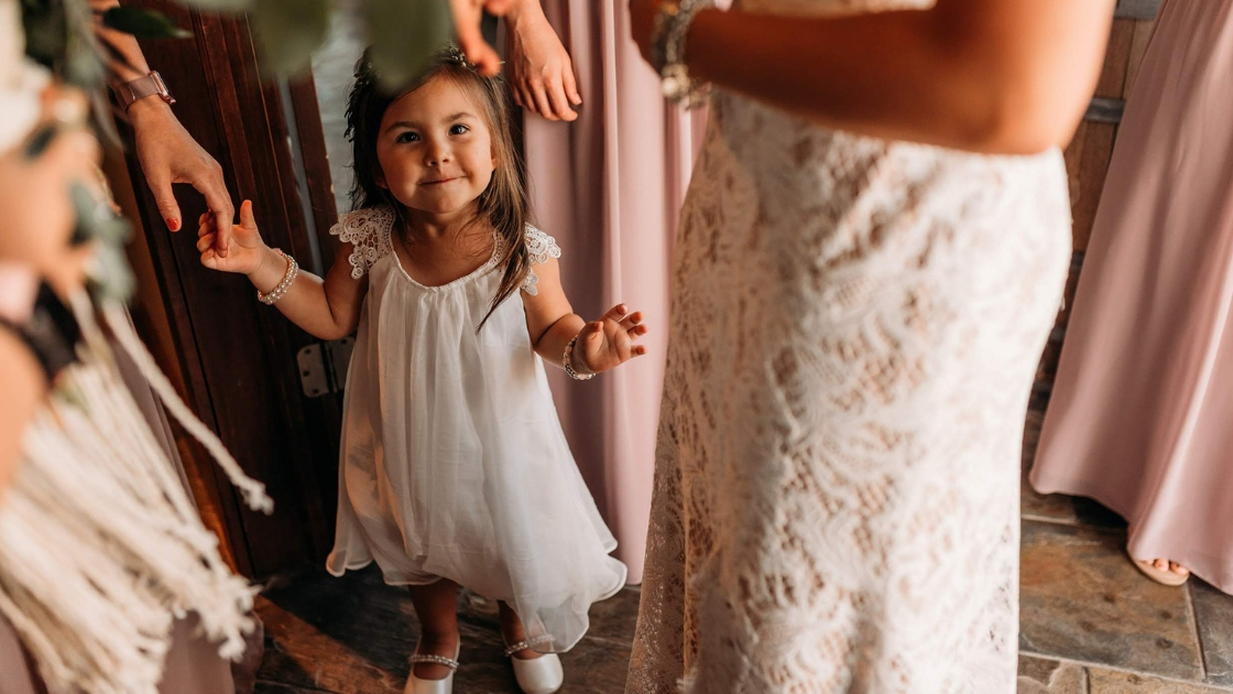 Flower girl in white dress stands with wedding party on wedding day mauve pink dresses around bridal party