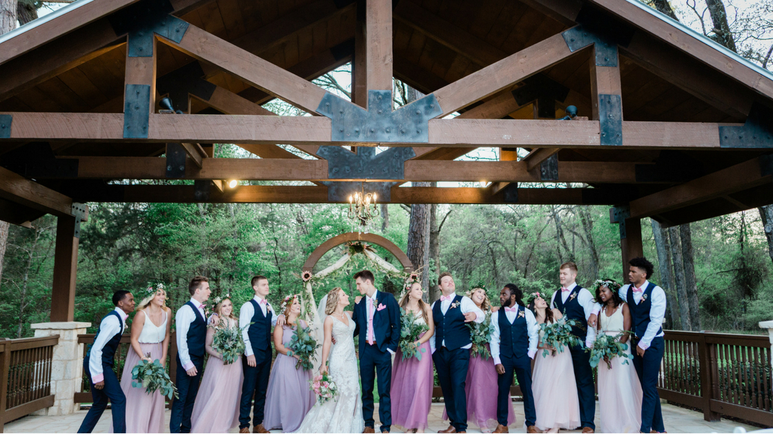 entire bridal party poses with bridesmaids in ombre tulle skylar skirts and ivory tops from Revelry.