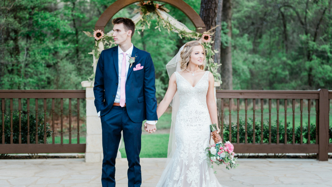 bride and groom pose for portraits post ceremony with natural forest background.