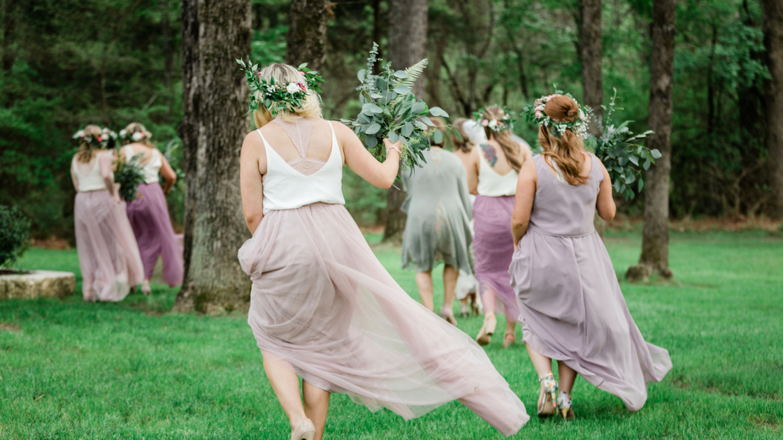 bridesmaids run off into the woods in ombre color story of blushes, purples, and neutrals.