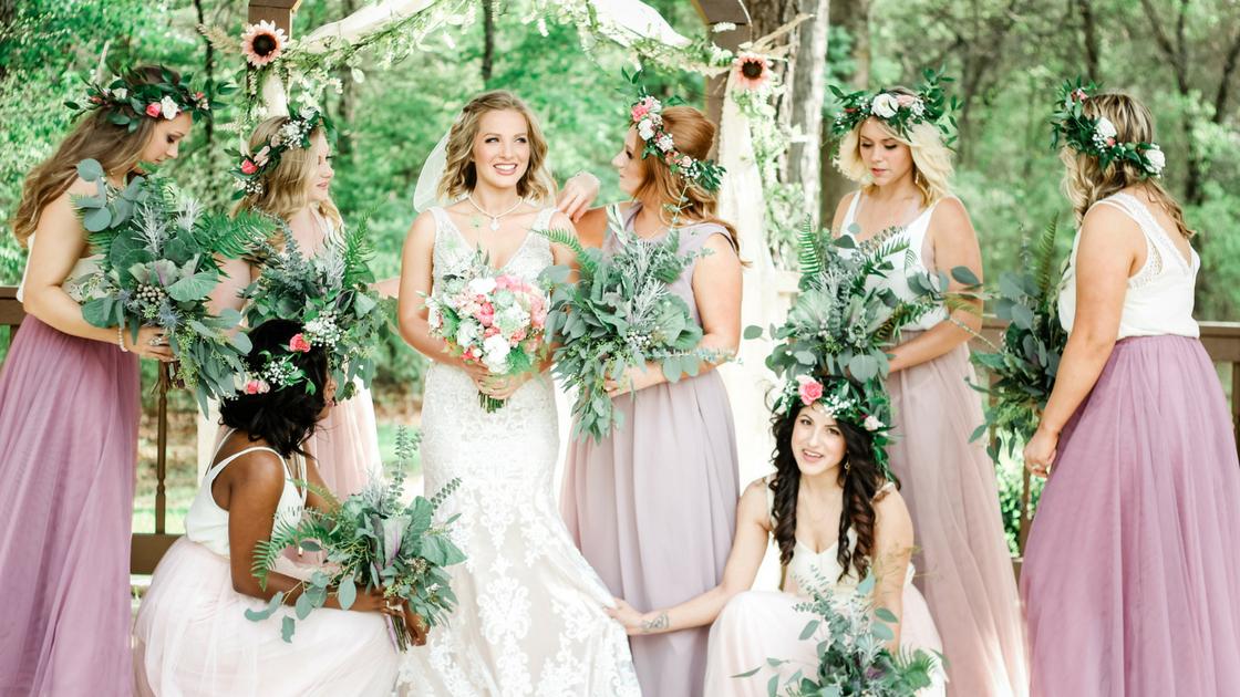 bridesmaids pose with bride with greenery florals and flower crowns plus tulle skirts and chiffon tops.