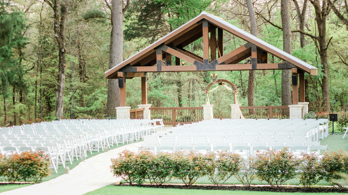 outdoor ceremony with white chairs, and wooden structure for this enchanted forest