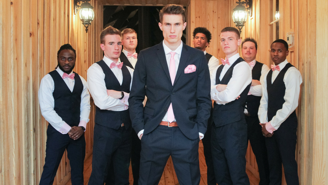 broom stands in front of groomsmen posing for photos in pink bow ties.