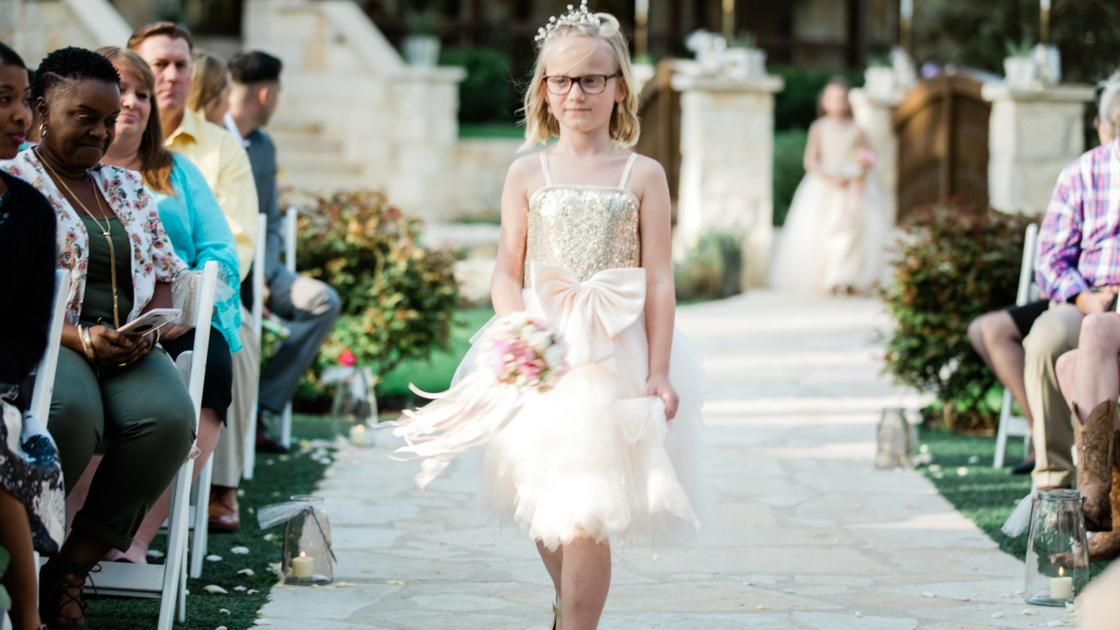 flower girl walks down the aisle in sparkly dress.