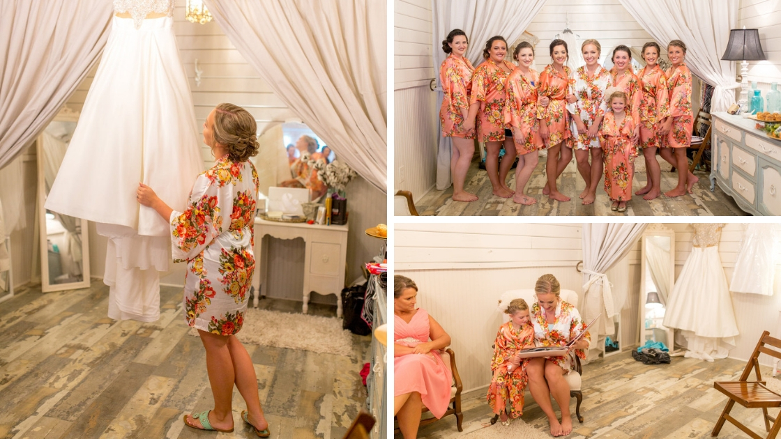 Bride in white floral robe looks at wedding dress and book and poses with her party