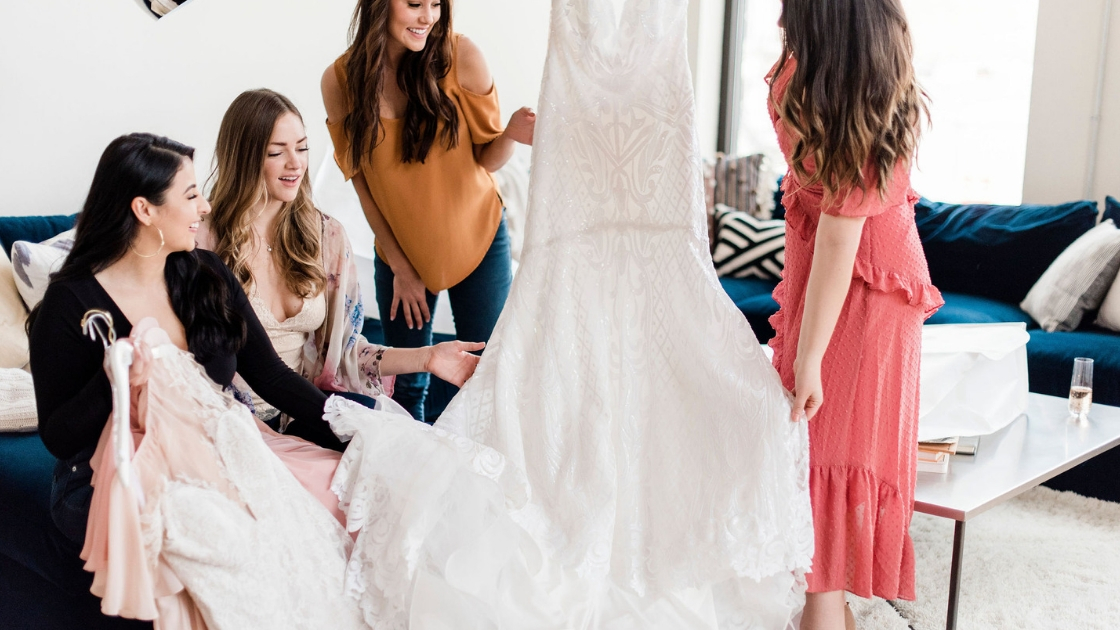 Girls in fashionable clothes in austin texas hold up gorgeous art deco wedding gown white dress with sequin details gorgeous look best friends picking out outfitts for wedding day checking colors and picking styles