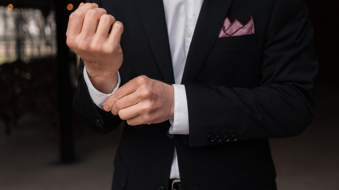 groom in black tux with pink burgundy pocket square cufflinks put on detail shot