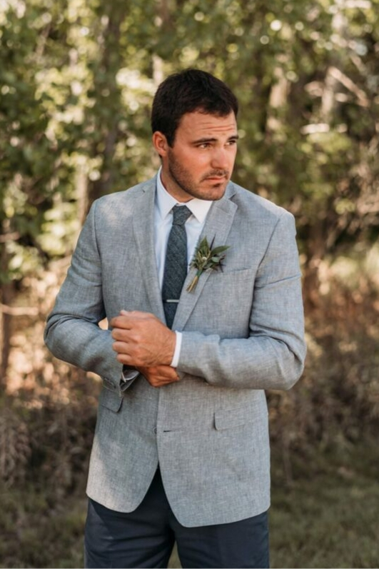 Groom on wedding day in grey suit jacket with stubble greenery boutineer getting ready for wedding ceremony
