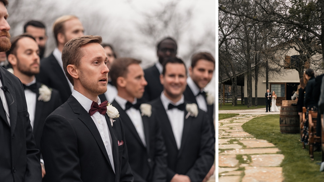 Groom with shocked expression stands at alter and waits for bride to walk down the aisle with father from rusic barn