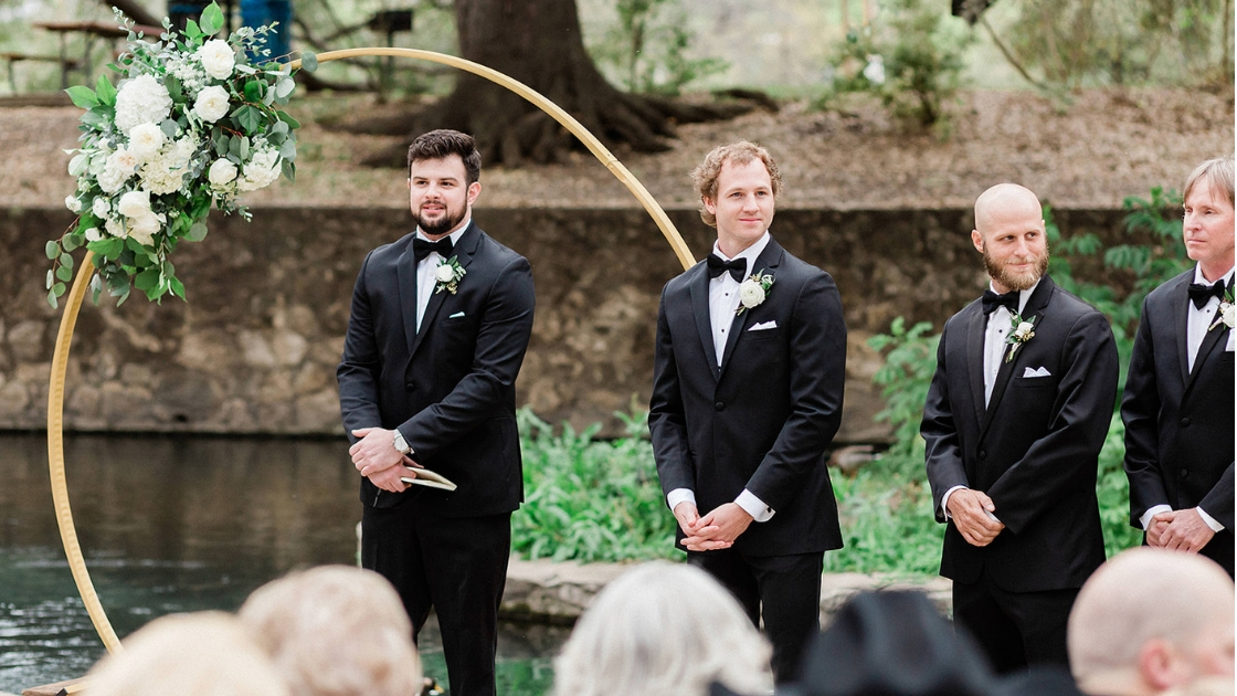 Groomsmen and groom tuxes black bowtie in front of circle alter looking down and wait for bride to walk down aisle