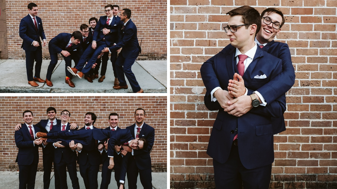 groomsmen in navy suits pose and laugh and hold up groom on wedding day
