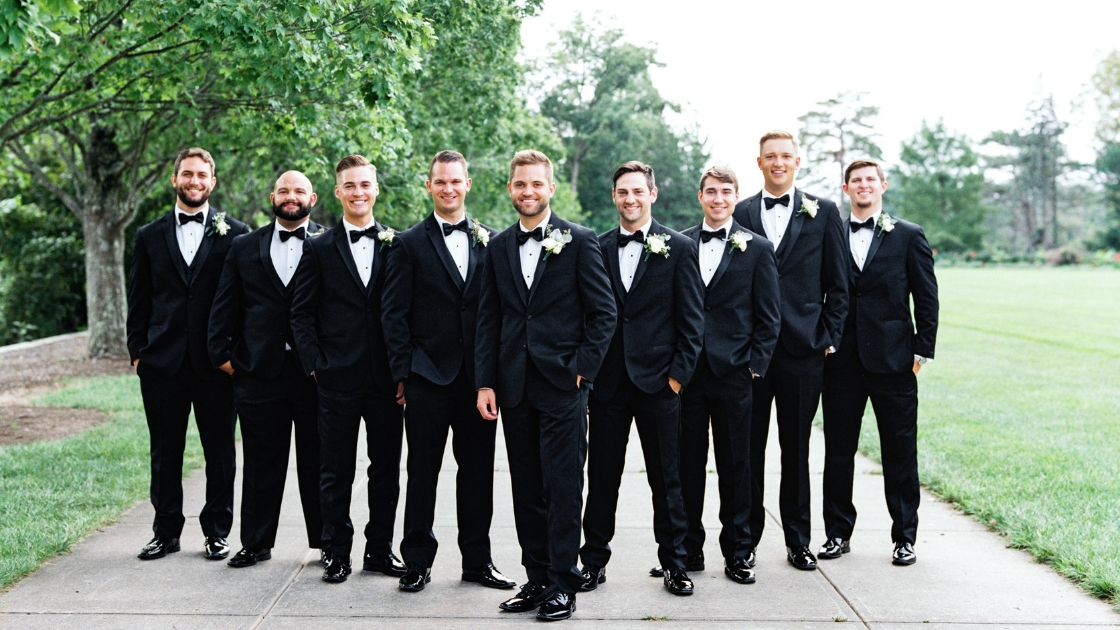 Groomsmen posing on wedding day in black tuxes smiling with hands in jacket wearing black tuxes 9 total men