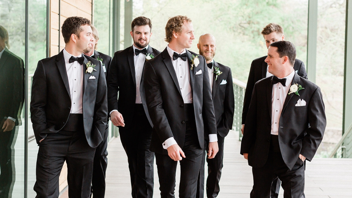 Groomsmen walking around after getting dresses and ready on wedding day white boutineer green leaf