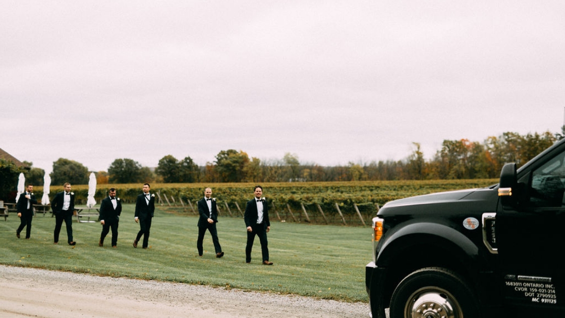 groomsmen walking to limo bus on wedding day getting ready for photos on wedding day