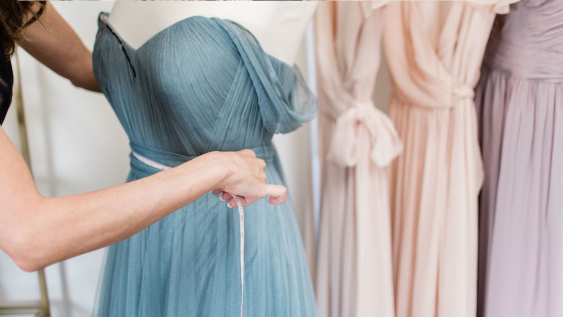 Hands using measuring tape to weap about the waist of a blue tulle bridesmaid dress made by revelry with rack sho4t in the back