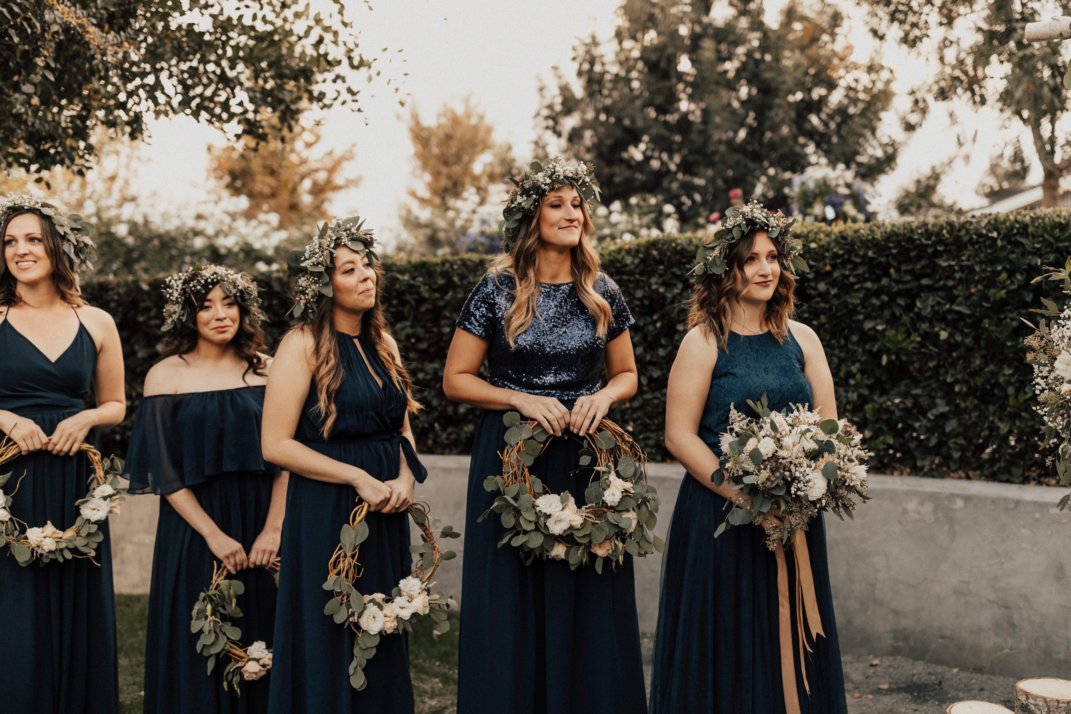 mix and match navy chiffon and navy sequin bridesmaid dresses and separates holding wreath bouquets.
