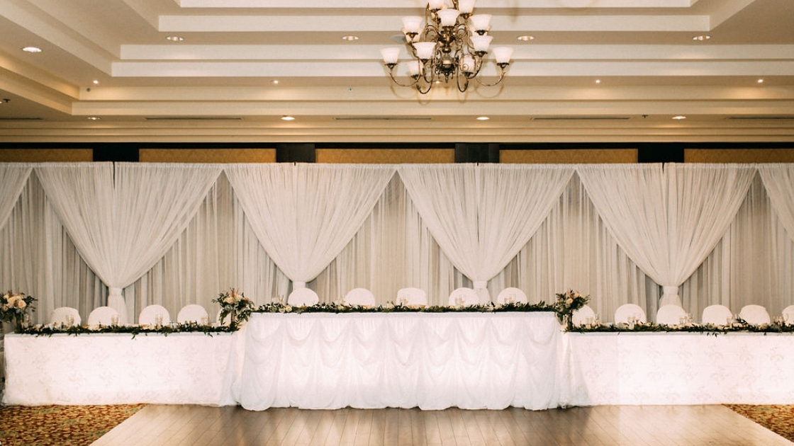 Head table at fall wedding in canada huge table for entire bridal party white with greenery and draped backdrop