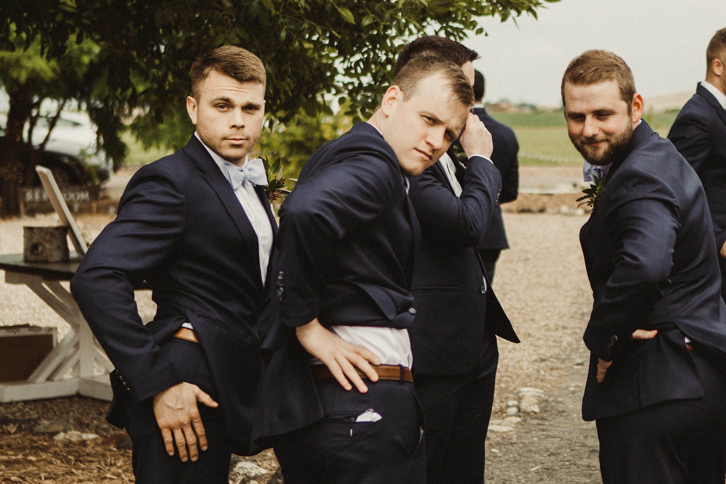 groomsmen pose in suits and act silly before a wedding