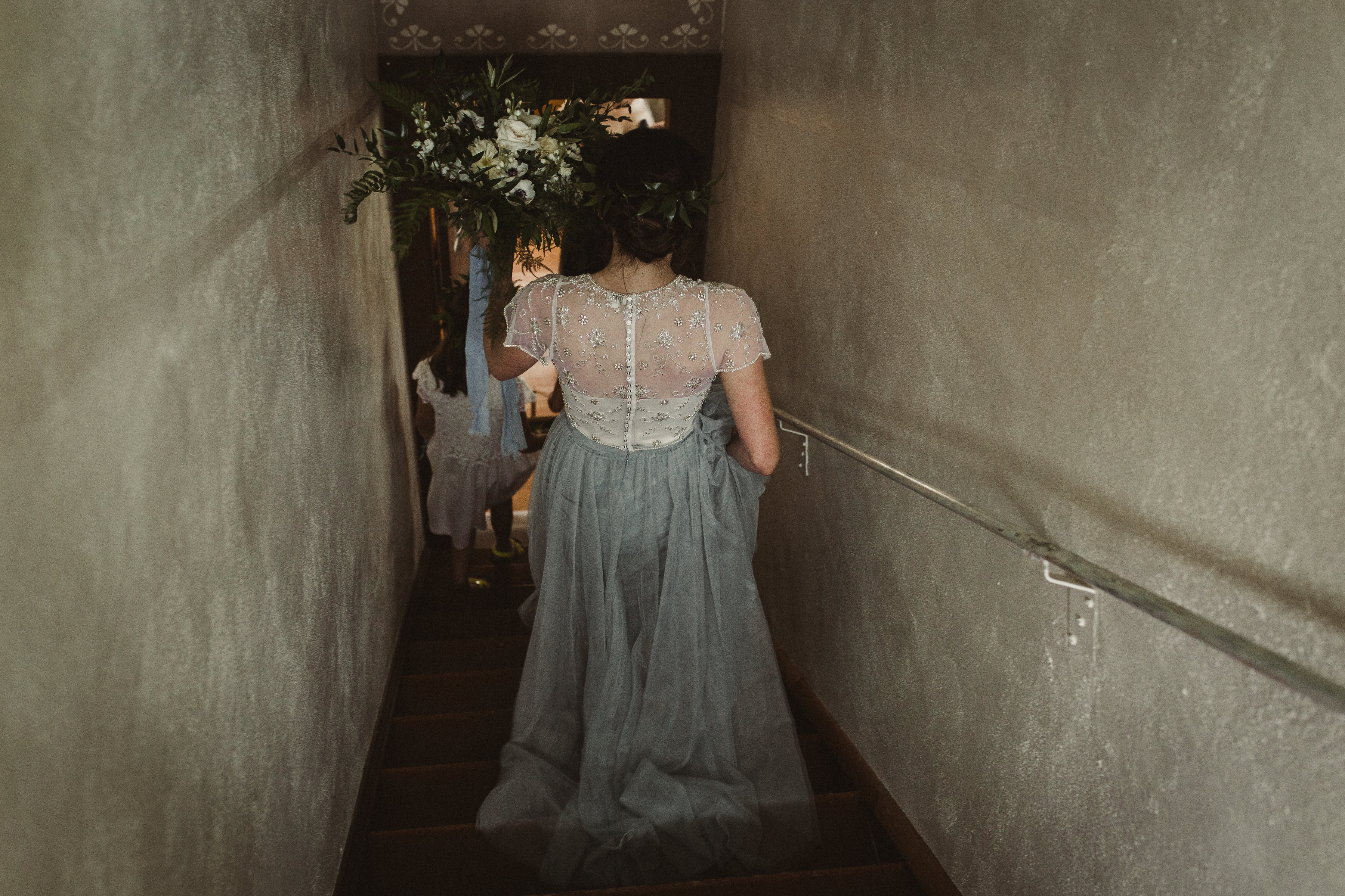 Bride is blue tulle skirt walks down stairs and goes to her wedding