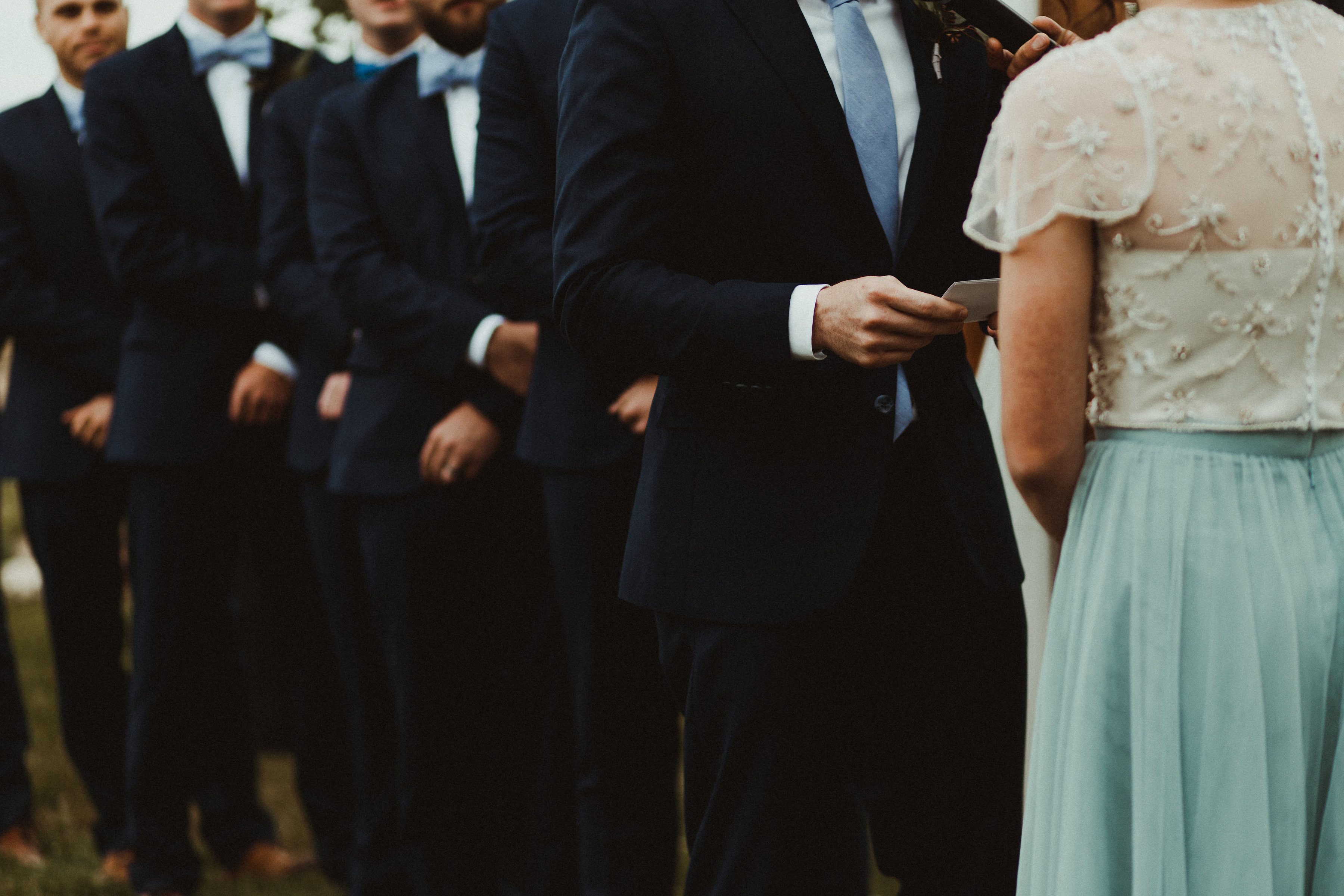 Groomsmen in suits stand by as the groom and bride in blue get married