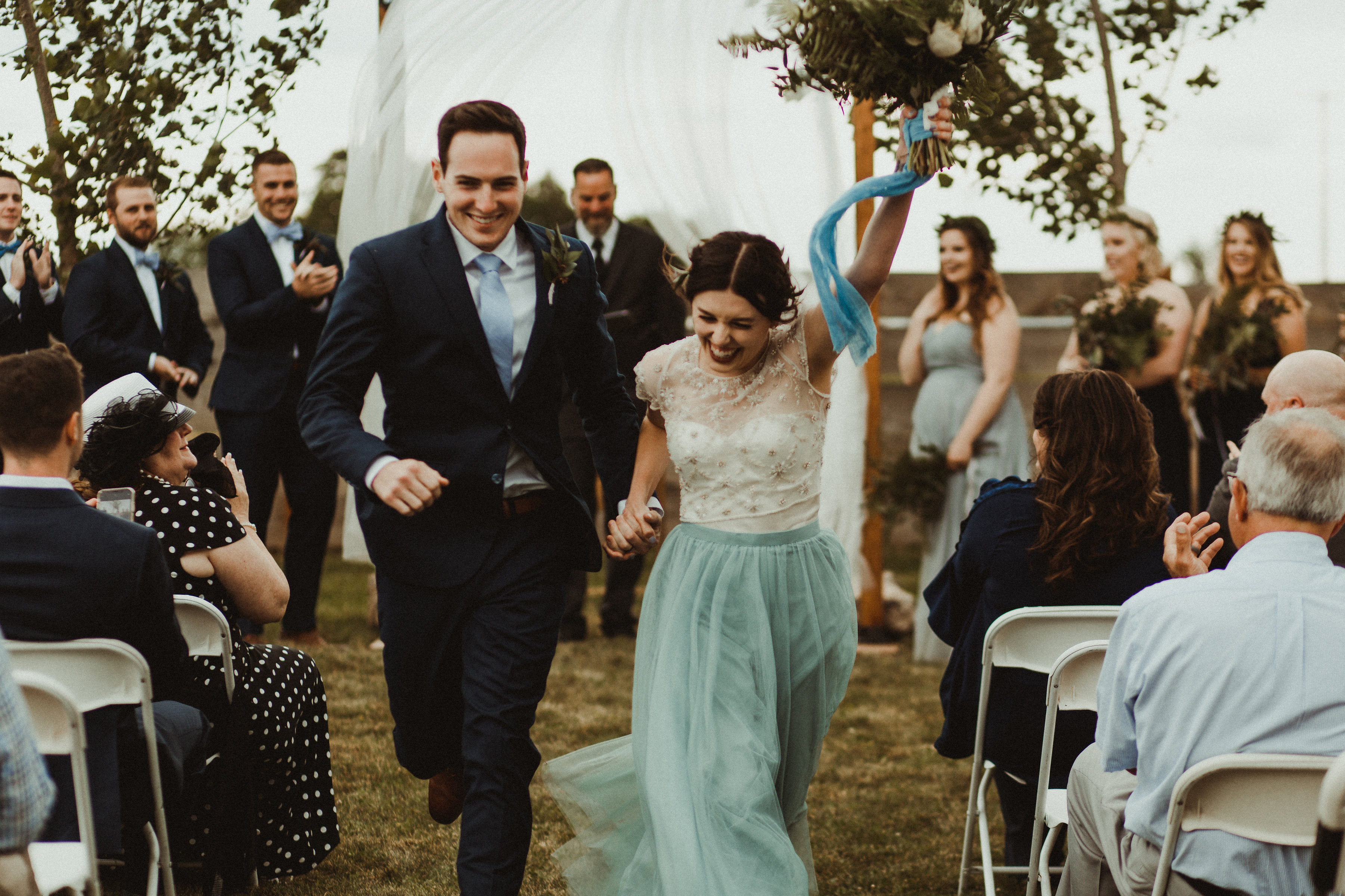 Bride in tulle and groom dance down the aisle celebrating their love