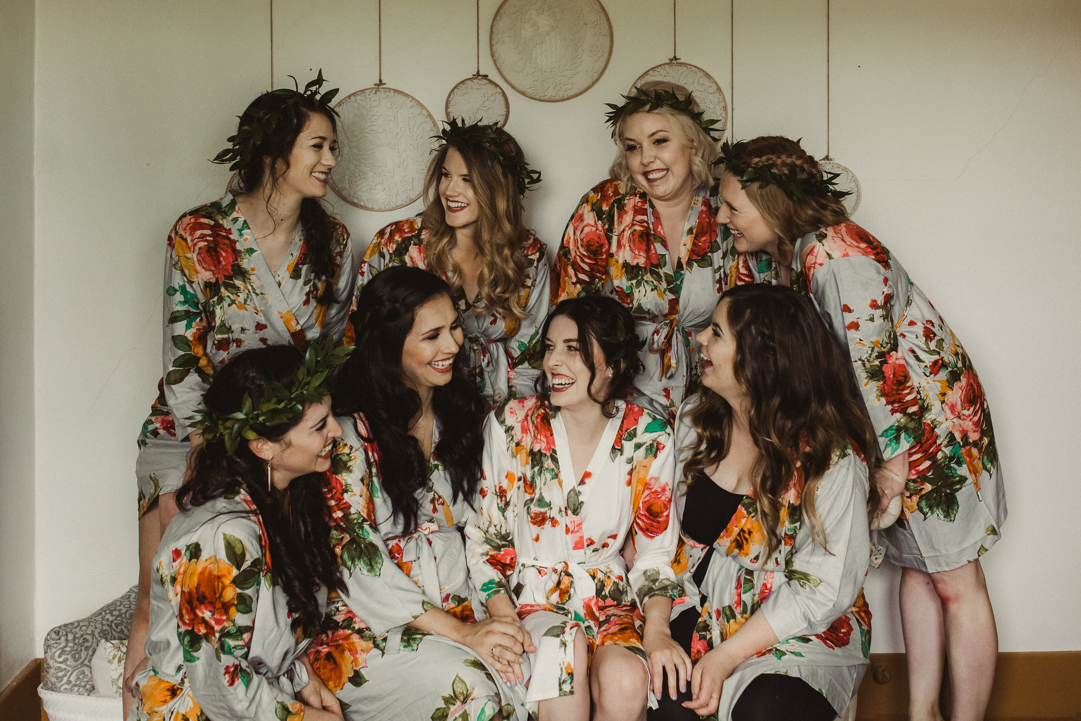 Bride and seven bridesmaids pose in floral robes and flower crowns