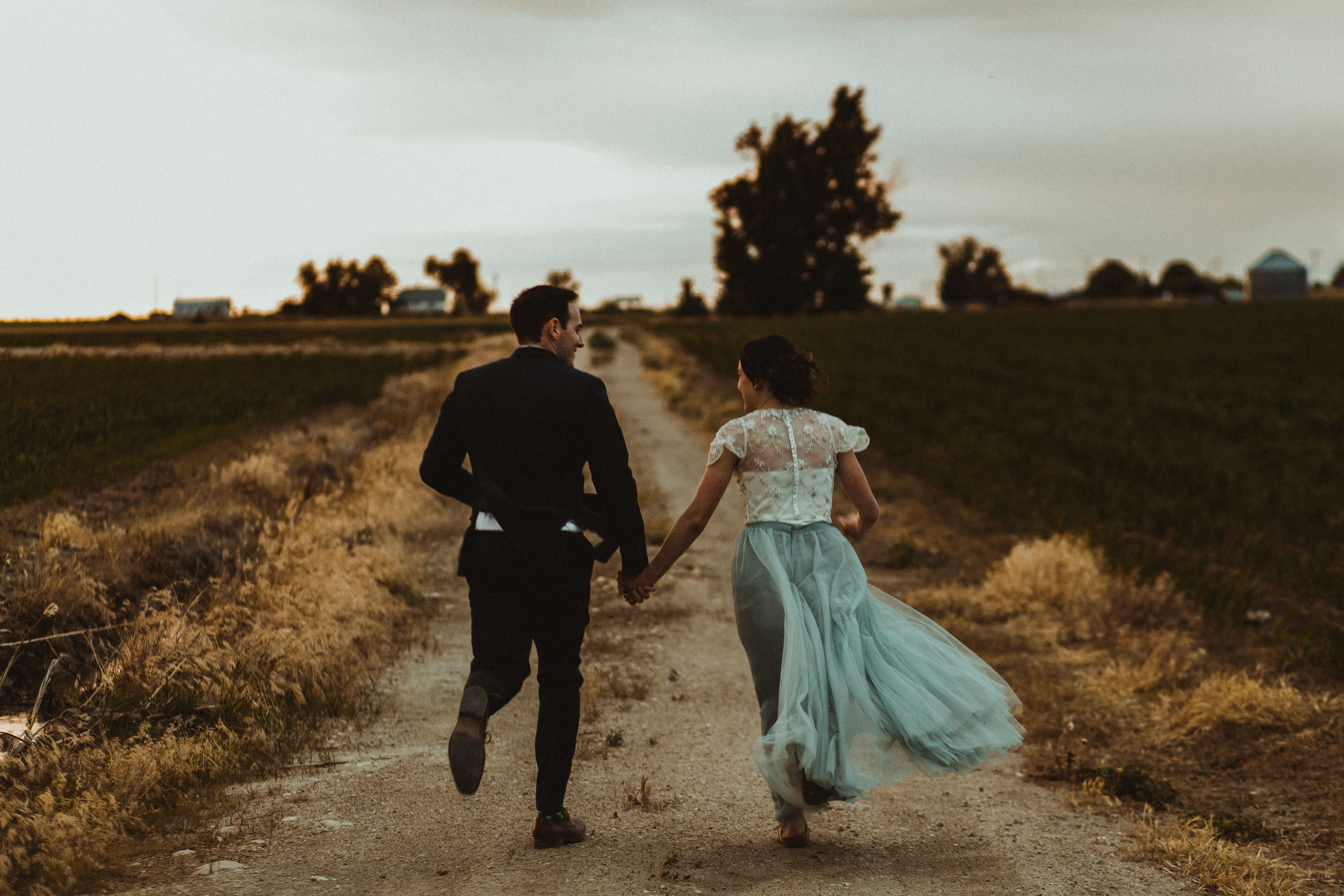 Bride wearing blue skylar tulle skirt runs into the sunset with groom