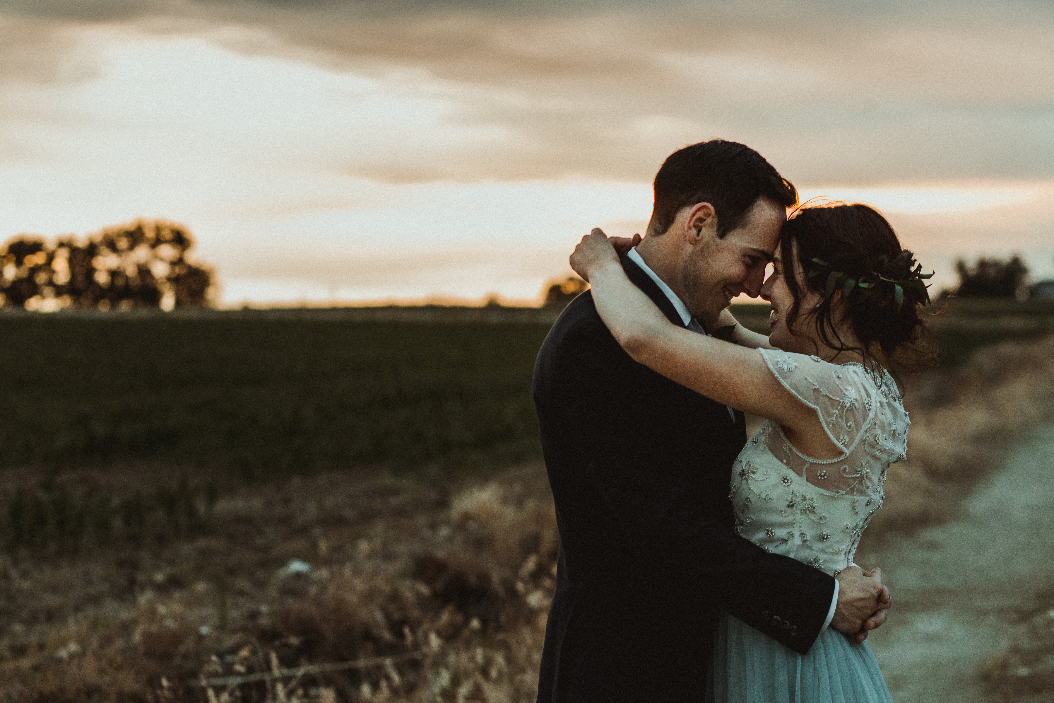 Newlywed couple hug in the sunset on their wedding night