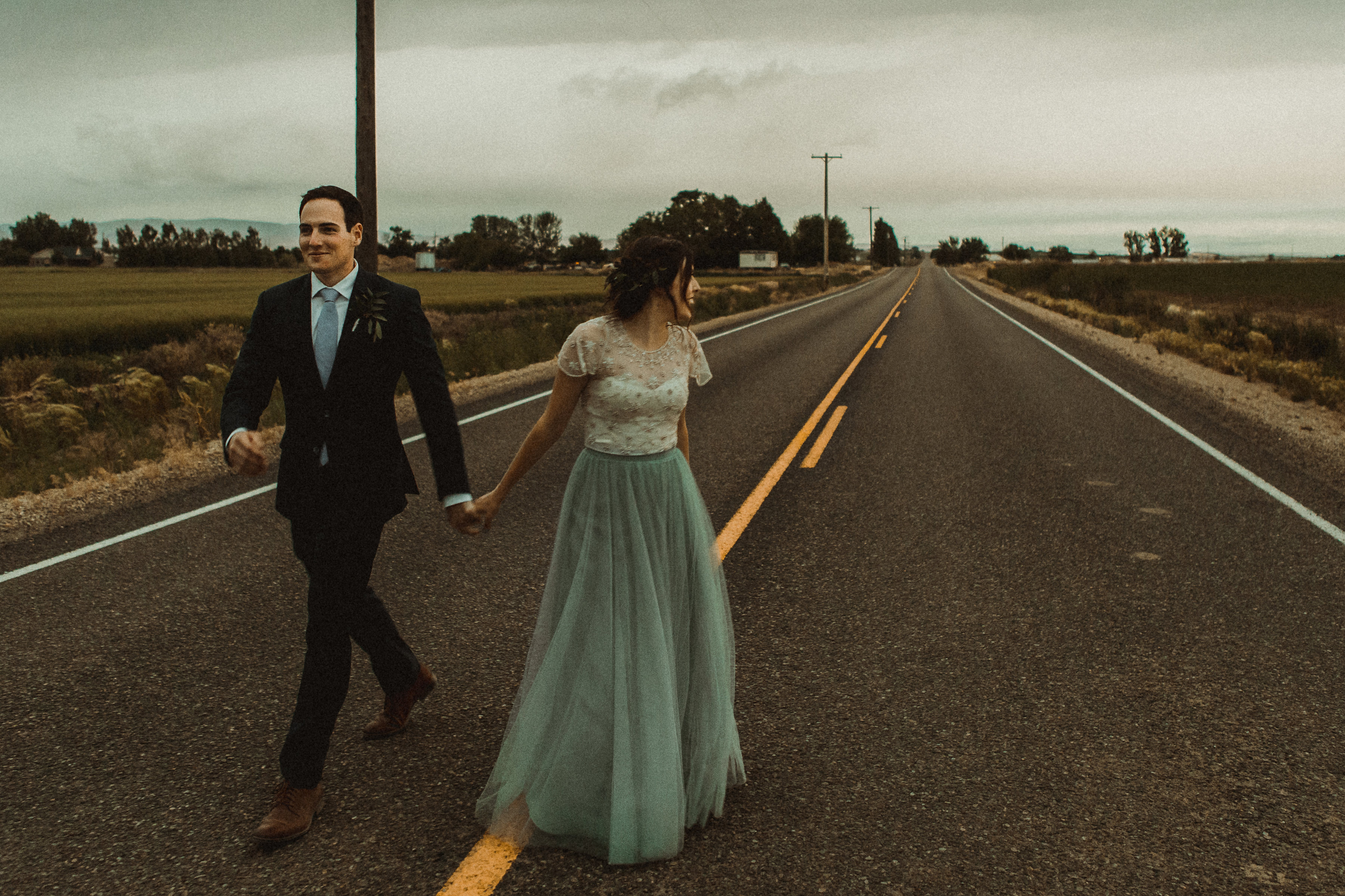 Bride in blue tulle skirt and groom take walk into sunset for photos