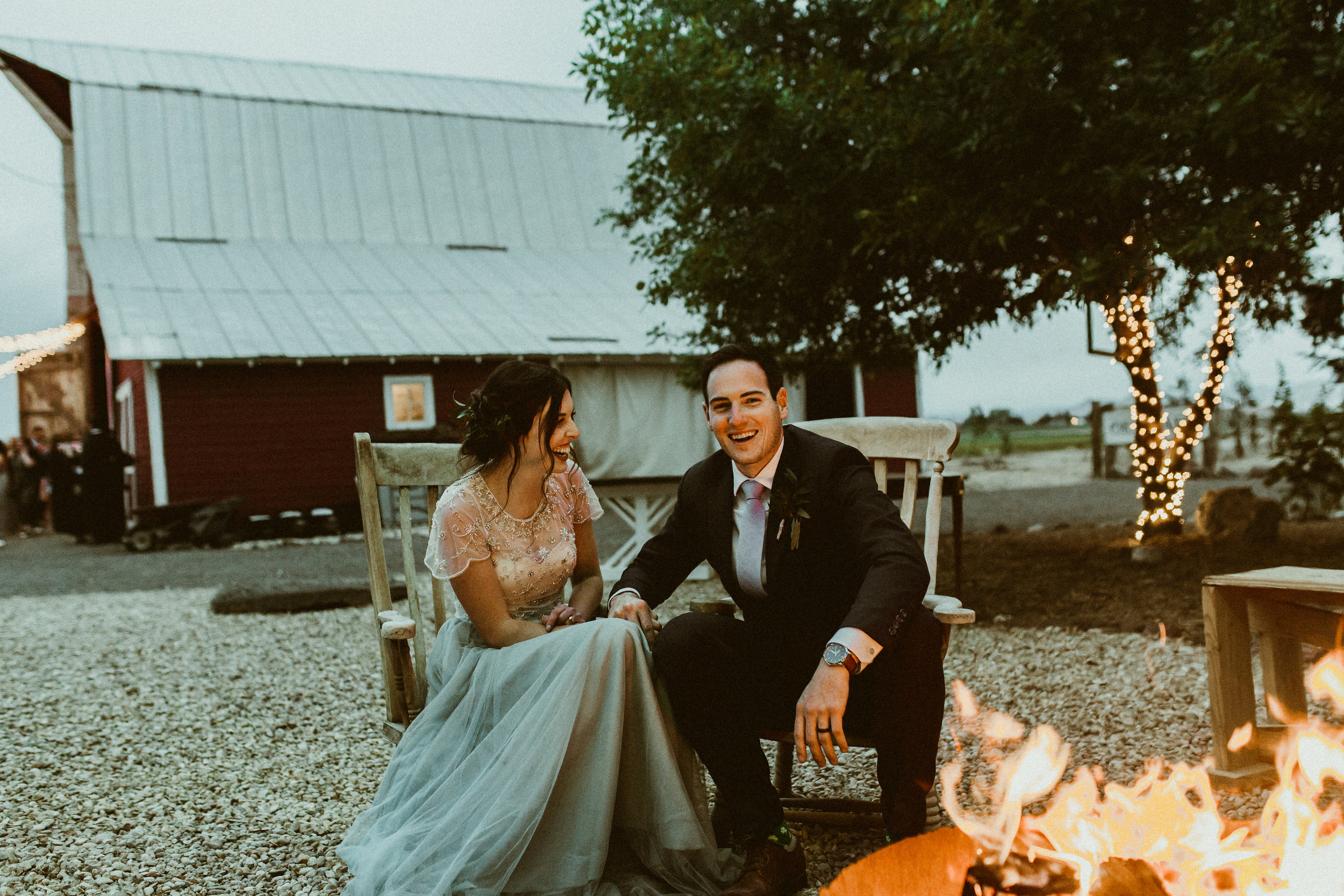 Bride in blue Revelry skirt sits with new husband in front of fire on wedding night