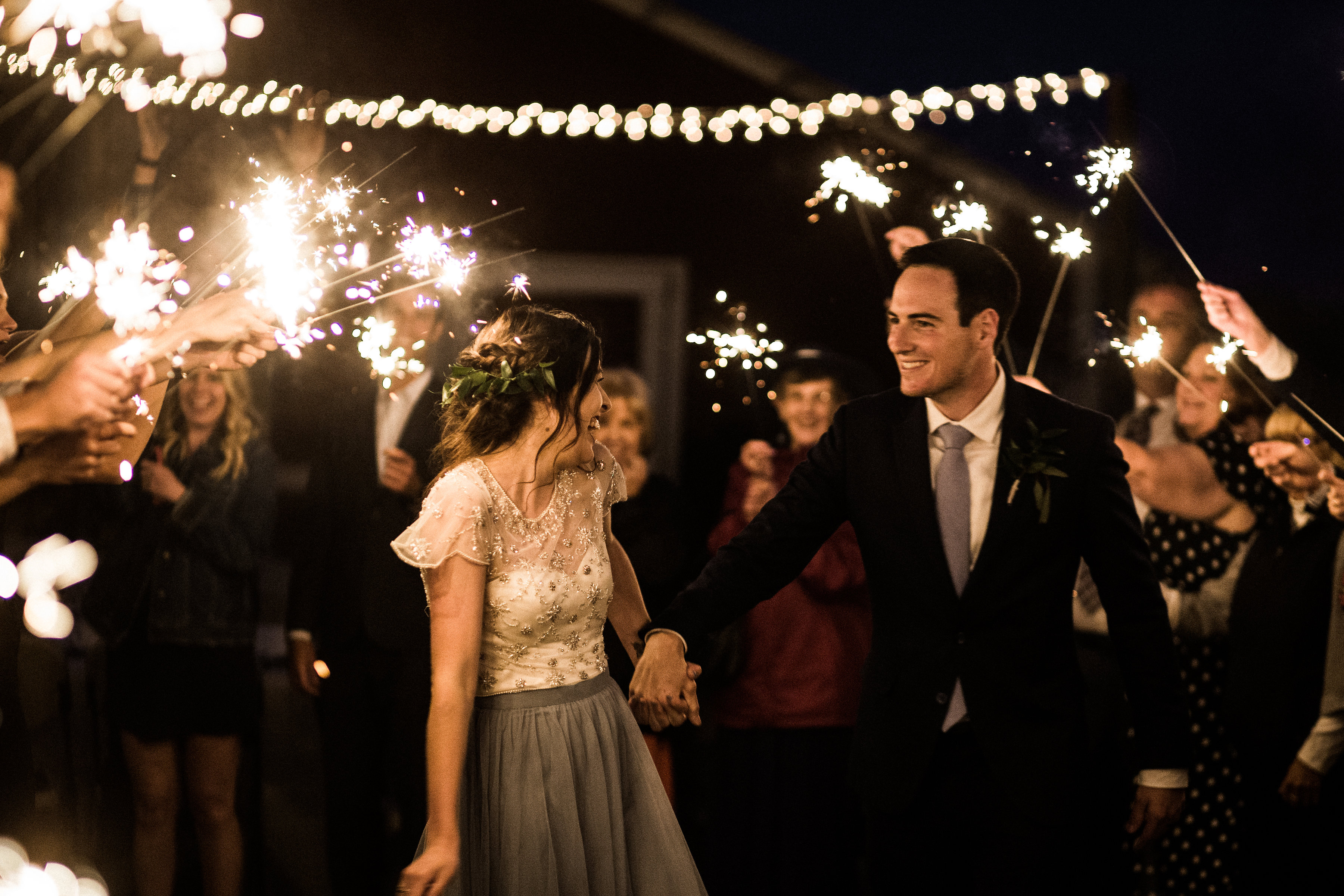 Bride in blue revelry skirt exit their wedding during a sparkler exit