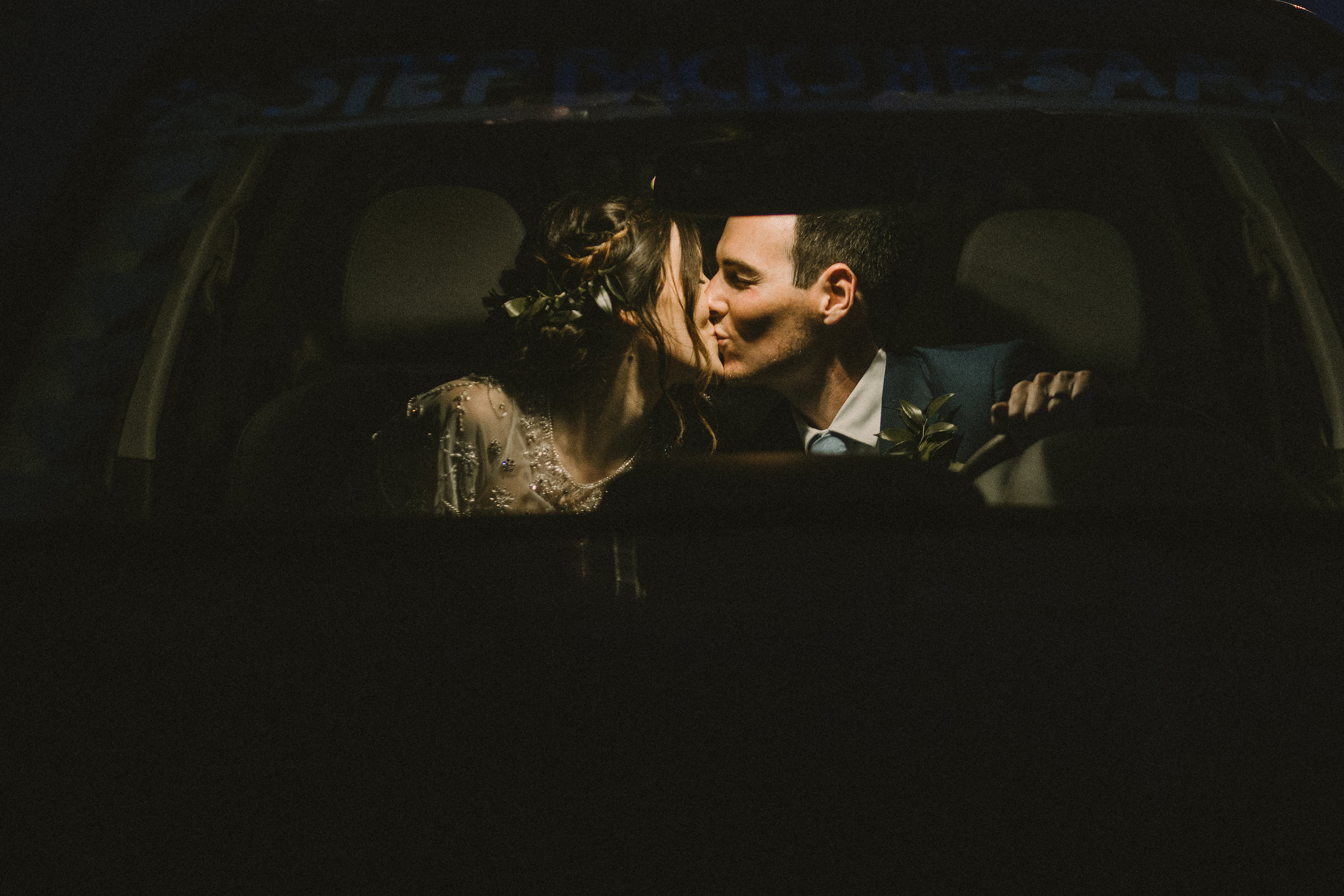 Bride and groom get in car and kiss as they leave their wedding as husband and wife