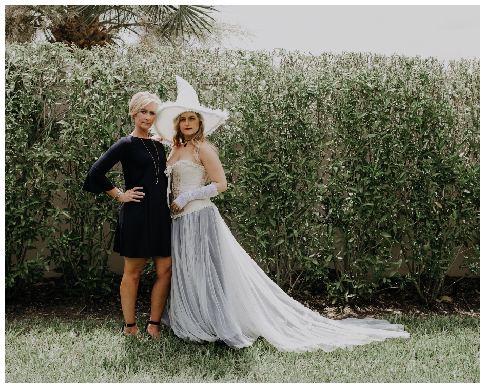 White witch with tulle train poses at bridal shower with bridesmaid in black