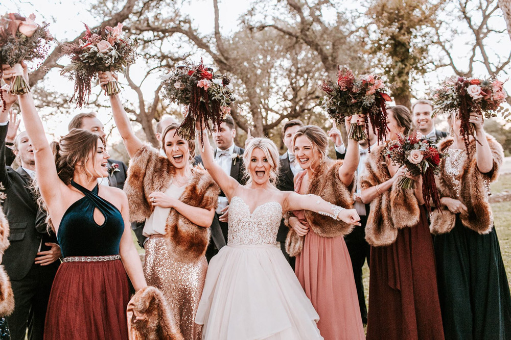 Revelry Bridesmaids cheering on the new couple wrapped in furs and bouquets raised high in celebration of this winter ceremony.